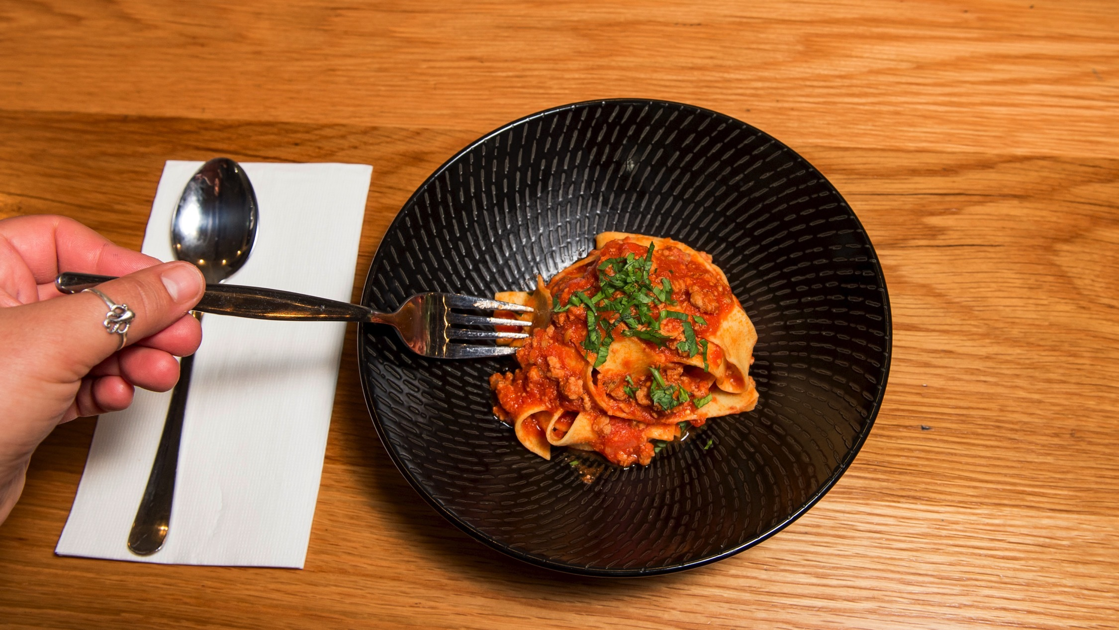 Hand holding fork eating pasta at Adamo's Pasta