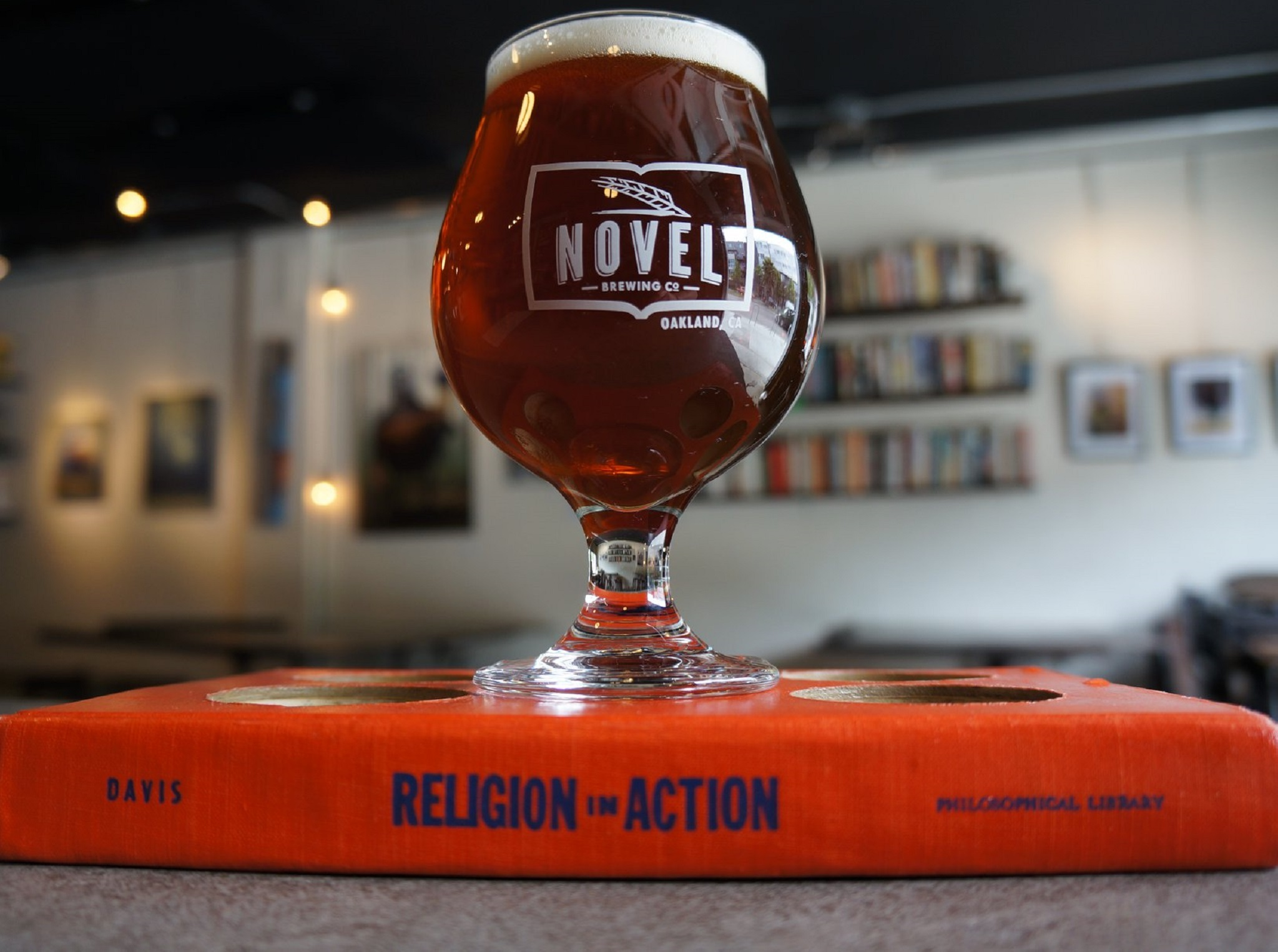 A beer on top of the book Religion in Action in a brewery