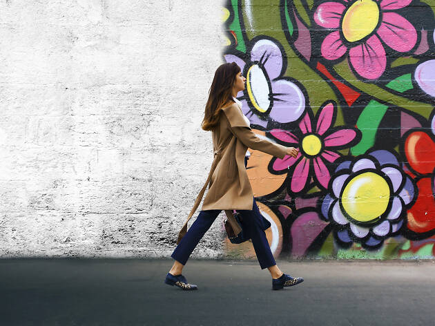 Woman walking next to wall with street art on it