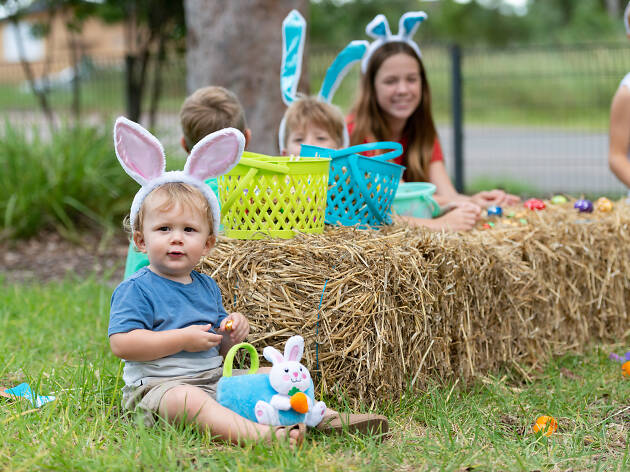 Kids sitting on hay bales with Easter toys.