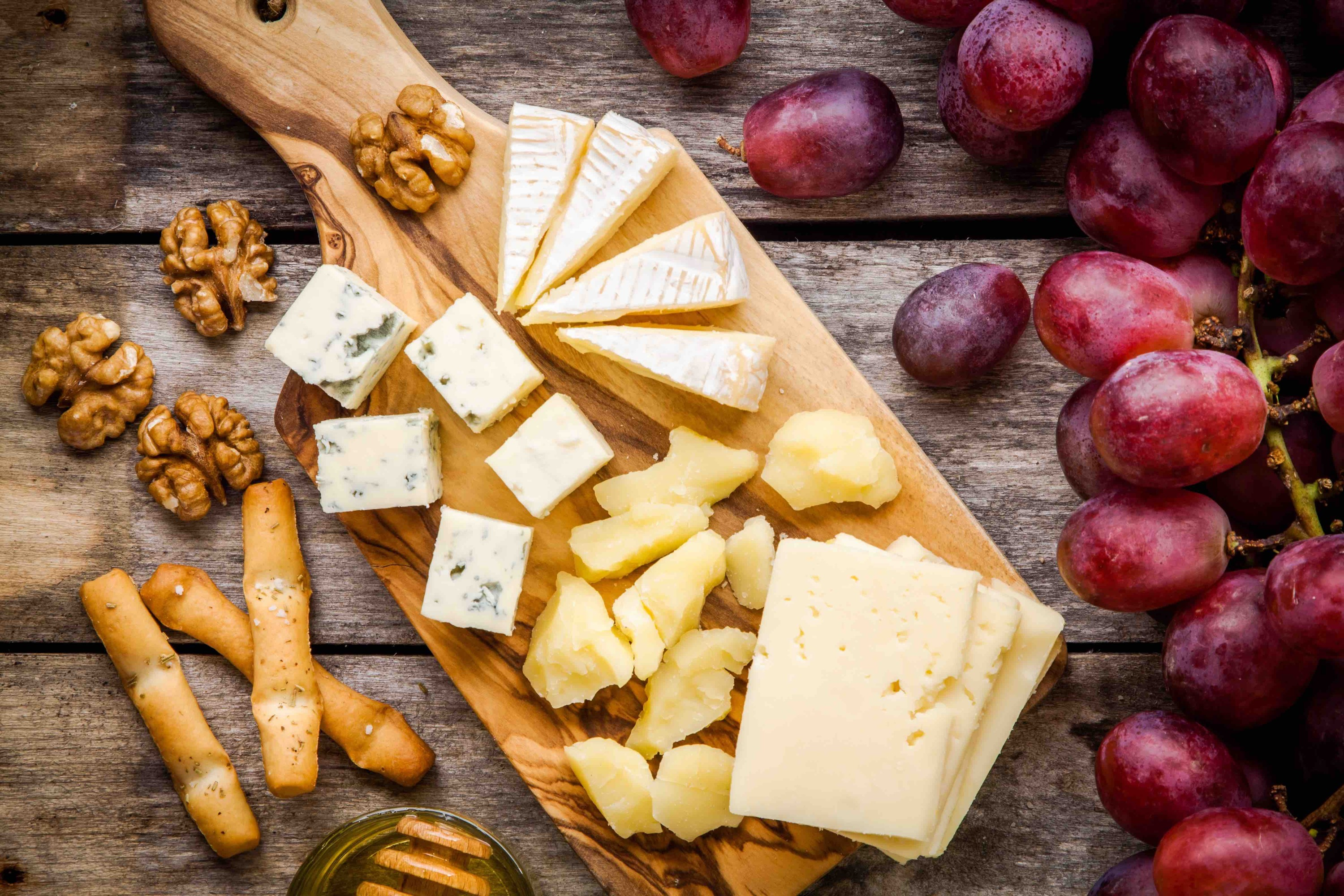 Cheese plate: Emmental, Camembert cheese, blue cheese, bread sticks, walnuts, grapes