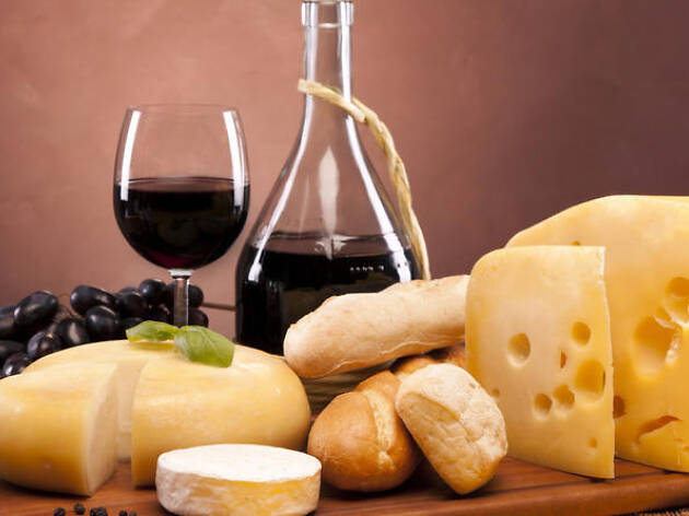 Table covered with a variety of cheeses and a bottle of red wine