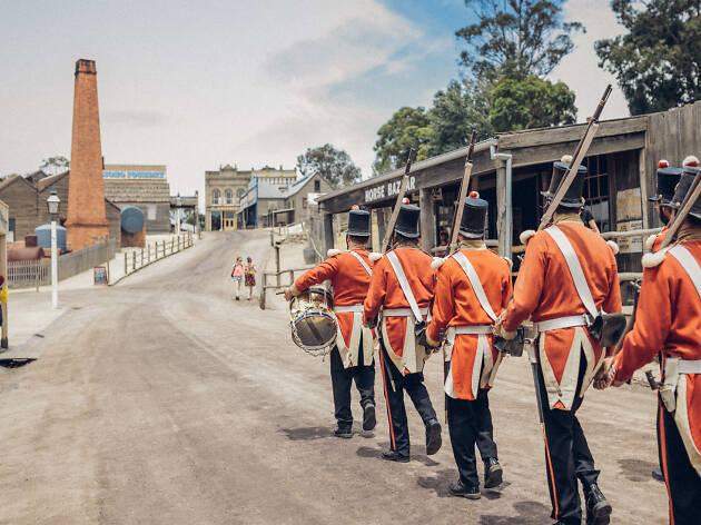 Men in old timey uniforms marching down street in Sovereign Hill