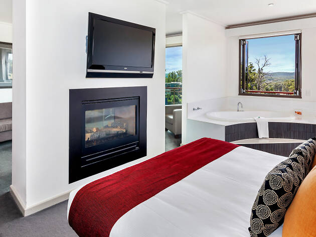 Bed in hotel room with fireplace and tv at RACV Goldfields Resort