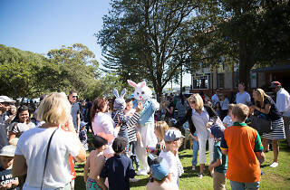 Families in the park with the Easter bunny.