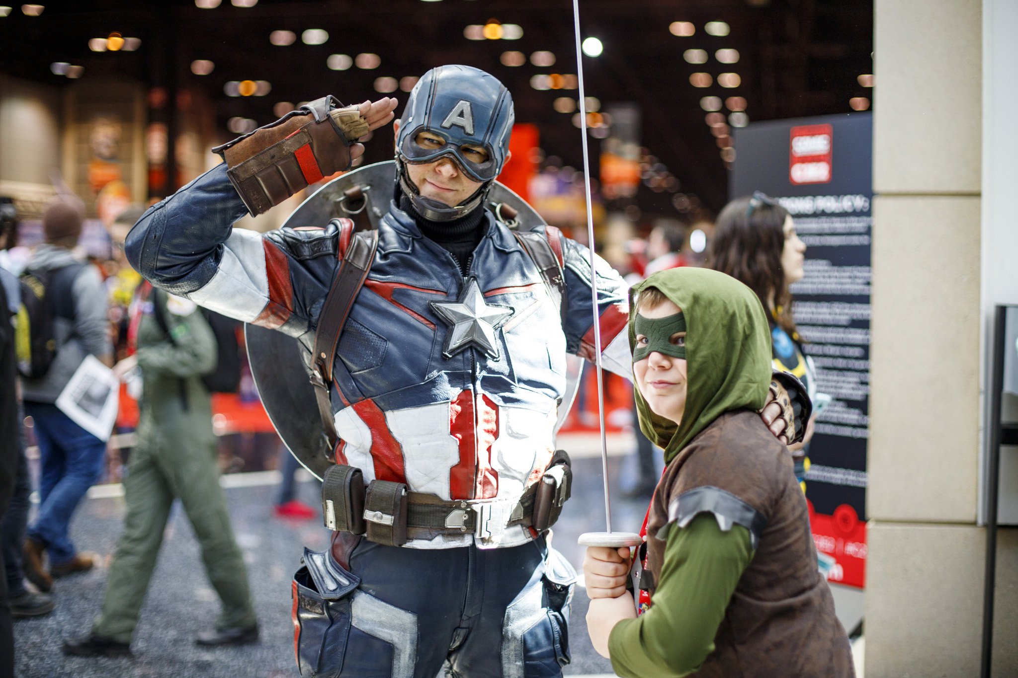 Discussing Fandom: Two cosplayers posing for a picture on the convention floor.