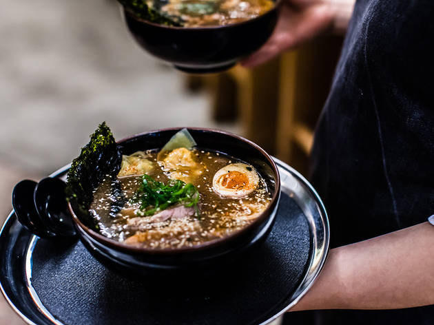 A bowl of ramen being held by waitstaff