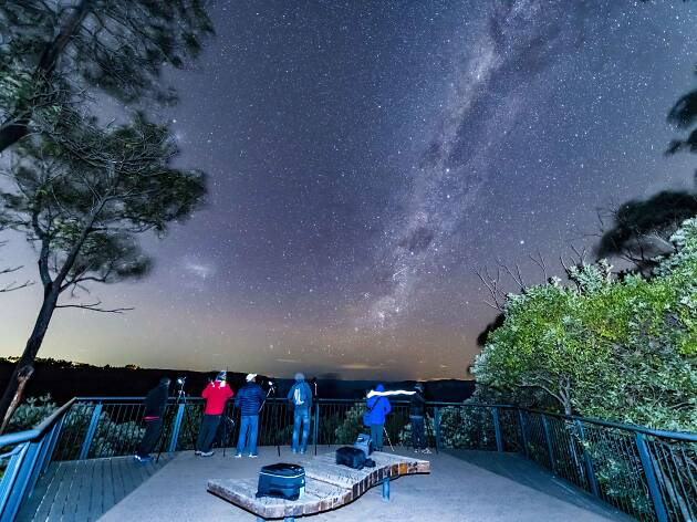 People taking photos of the nights sky from a lookout in the bush.