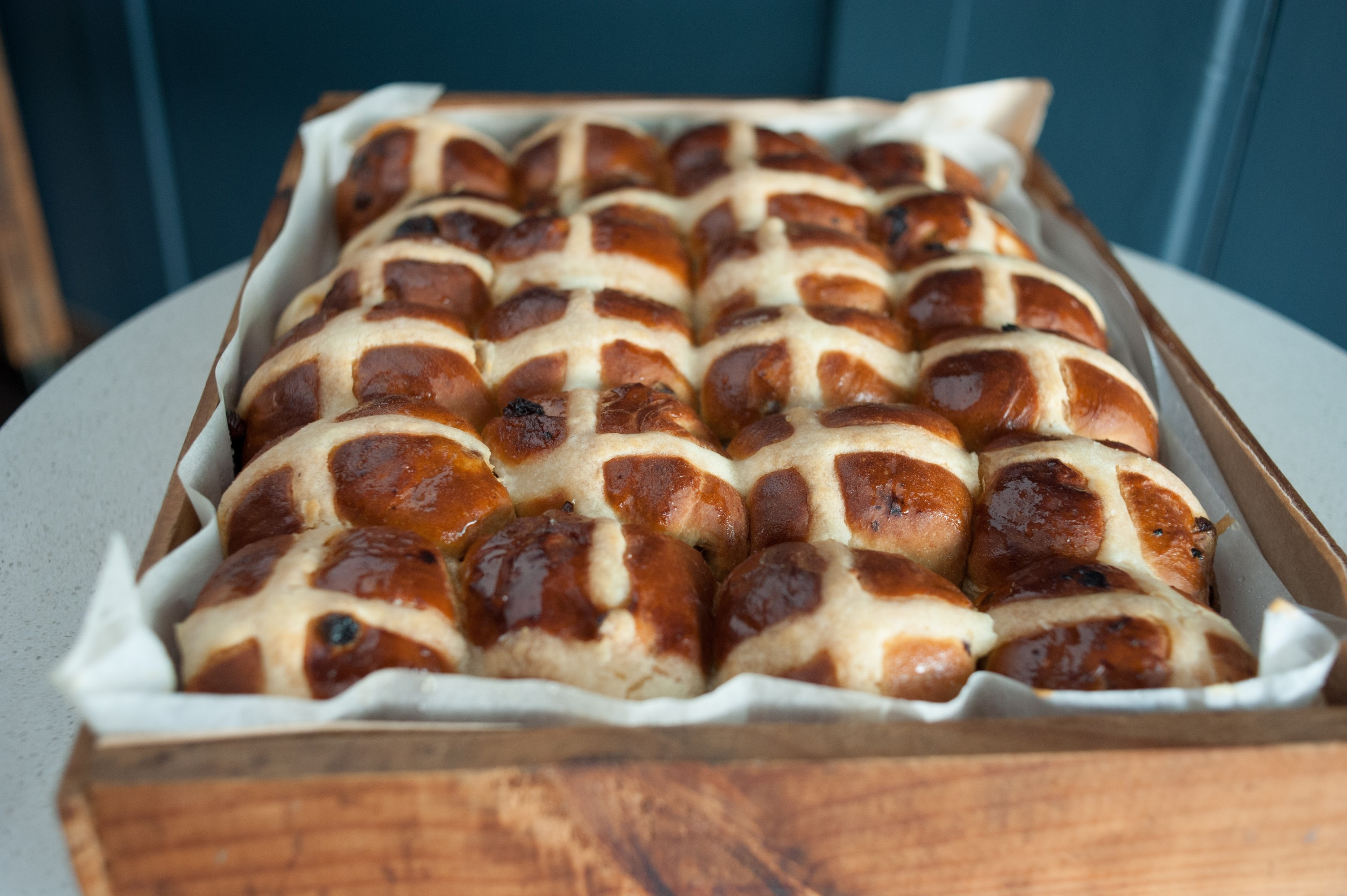 A wooden tray of hot cross buns