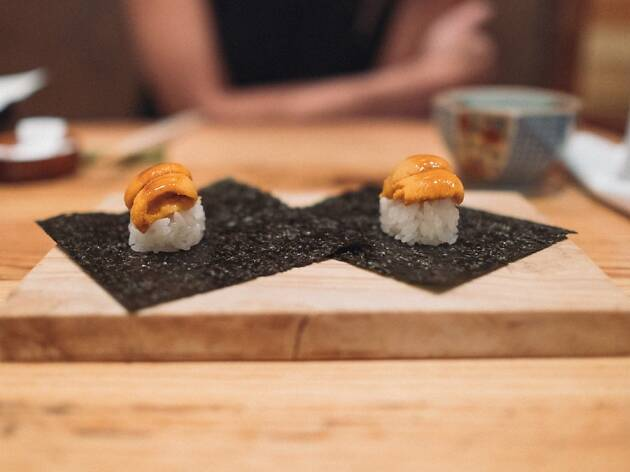 Two pieces of sushi with uni on top of rice on a wooden board