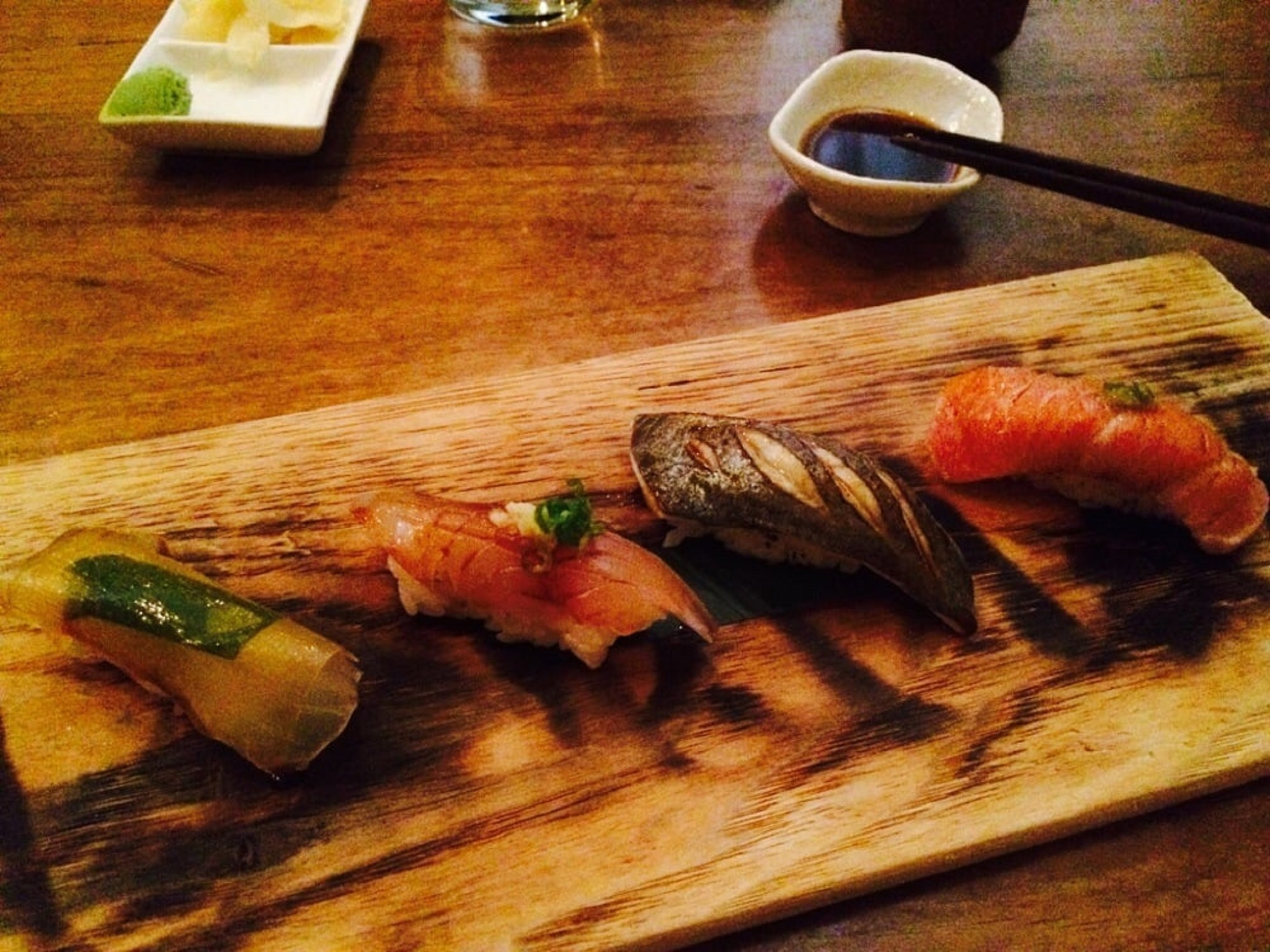 Four pieces of sushi on a wooden board with chopsticks on a dish of soy sauce