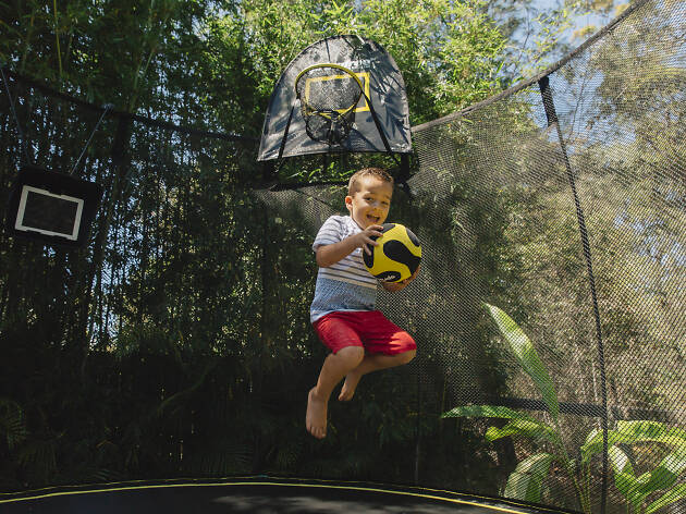 Kid jumping on a trampoline with a ball.
