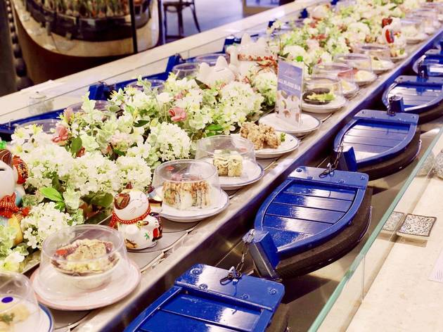 A sushi train that uses tiny boats in a canal instead of rails