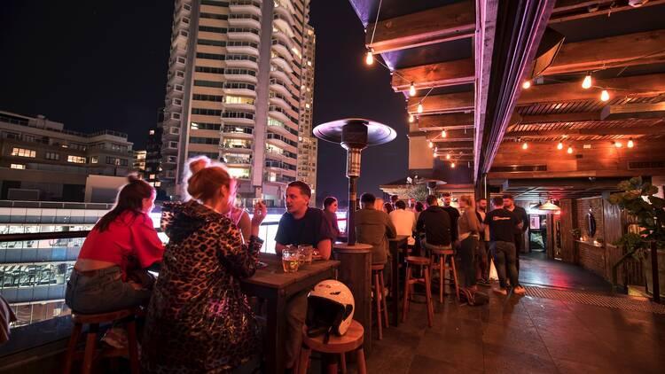 People sitting on rooftop at Kings Cross Hotel