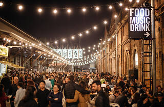 People walking under fairy lights at the Carriageworks Night Market.