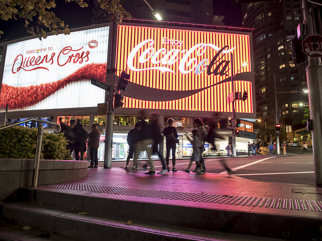 People walking at night in front of the Coke sign at Kings Cross