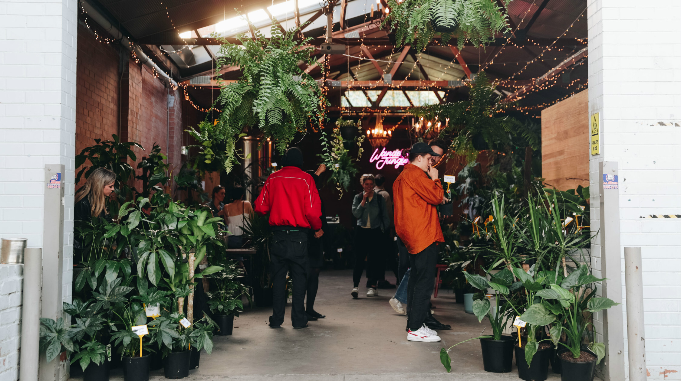 People wandering around garage filled with plants
