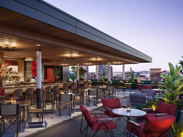 The roofdeck at Everdene with a view of the skyline and red lounge seating