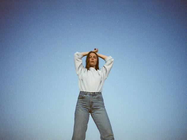 Maggie Rogers standing on a blue background.