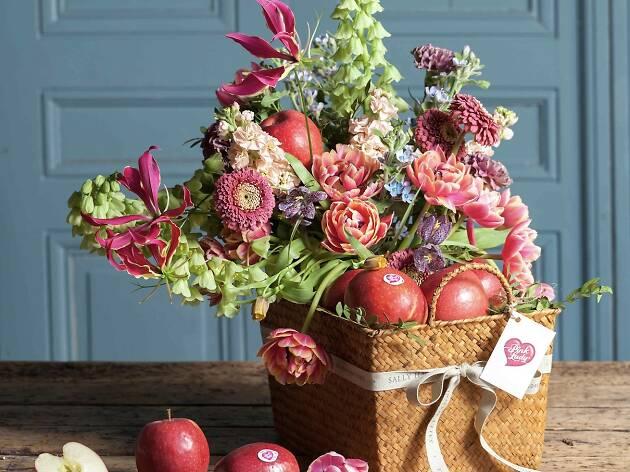Sally Hambleton y Pink Lady cesta de flores y frutas