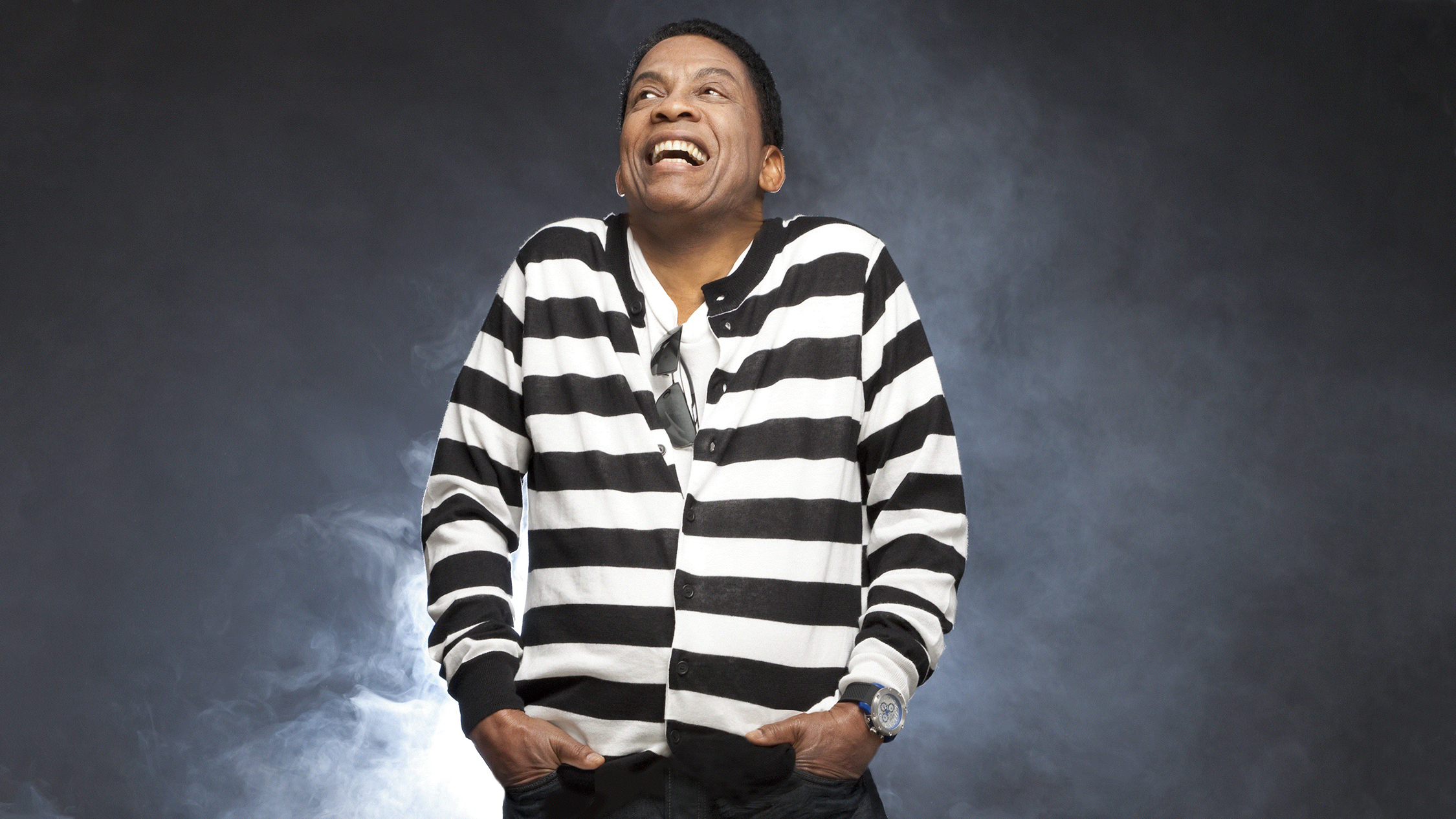 Herbie Hancock in a striped shirt laughing.
