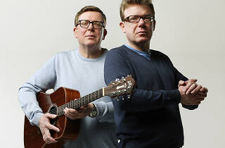 Craig and Charlie Reid posing with a guitar.