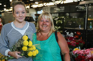 Two women holding flowers at the flower market.