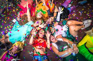 People in costume on the floor with confetti falling.