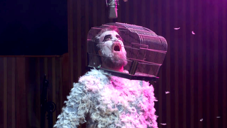Person with gage on head, covered in feathers, John Grant, 'Love Is Magic' 2018 album cover