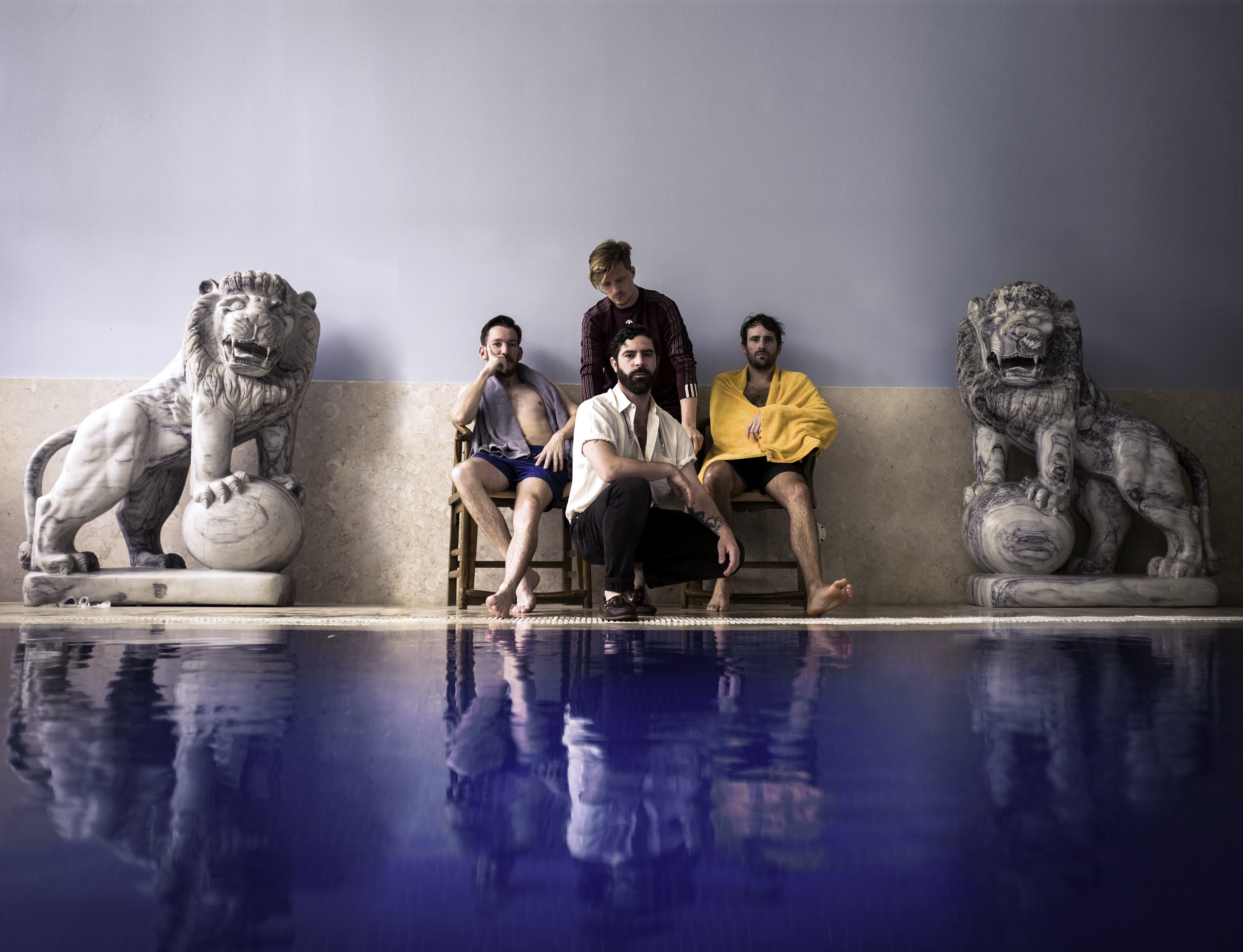 Foals the band sat behind a pool with statues of lions either side