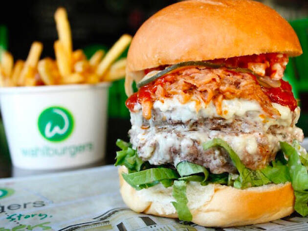 A large super melt burger from Wahlburgers, with fries in background