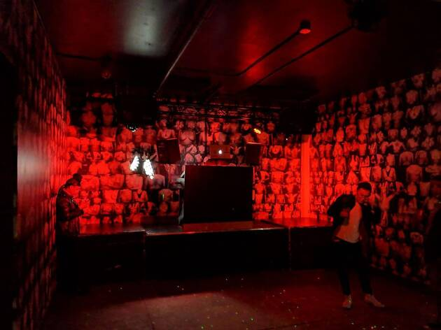 A red lit dance floor with photos of breasts papering the walls