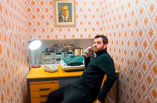Mike Skinner sat at a desk holding a phone to his ear