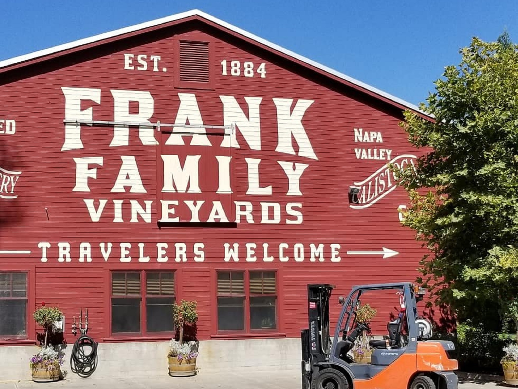 "A red barn with ""Frank Family Vineyards, Travelers Welcome"" in big white letters"