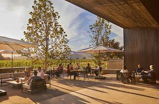 A modern patio with tables and white umbrellas overlooking vineyards
