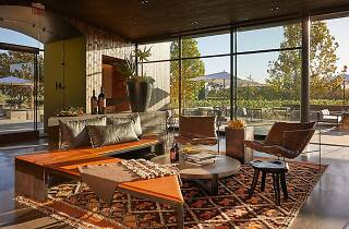 Tasting room with orange seating, a colorful rug and floor to ceiling windows looking out on a patio and vineyard