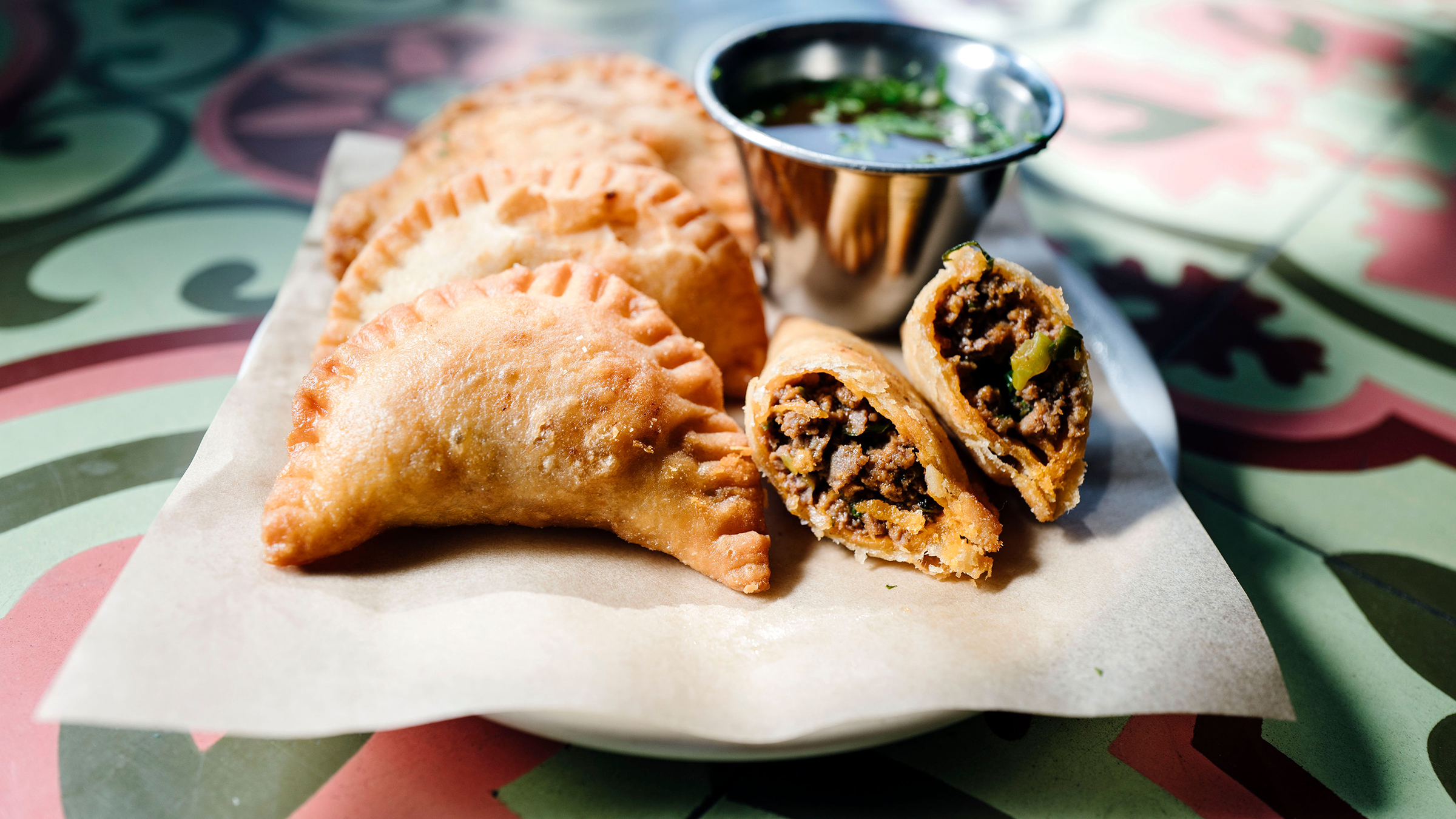 <p>Empanadas of dry-aged ground beef, green onions and smoked paprika with Brazilian hot vinegar</p>
