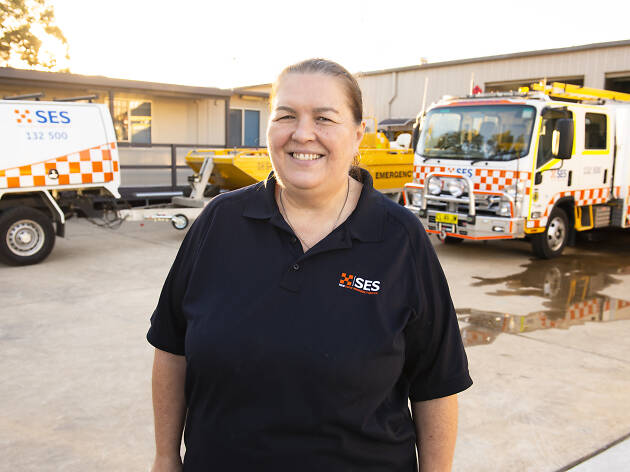 State Emergence Service volunteer Kathy Garancsi stands in front of SES trucks