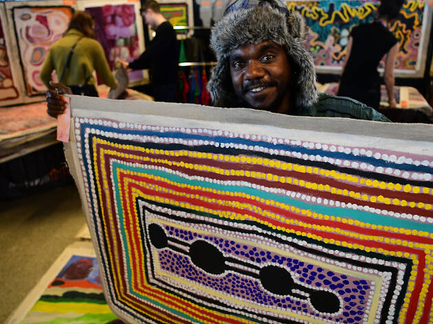 Aboriginal man holding a colourful textile work in front of other artworks.