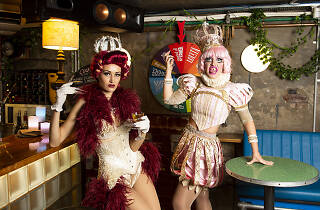 Porcelain Alice (left) Malena Dali (right) wearing costumes standing at the bar at Knox Street Bar