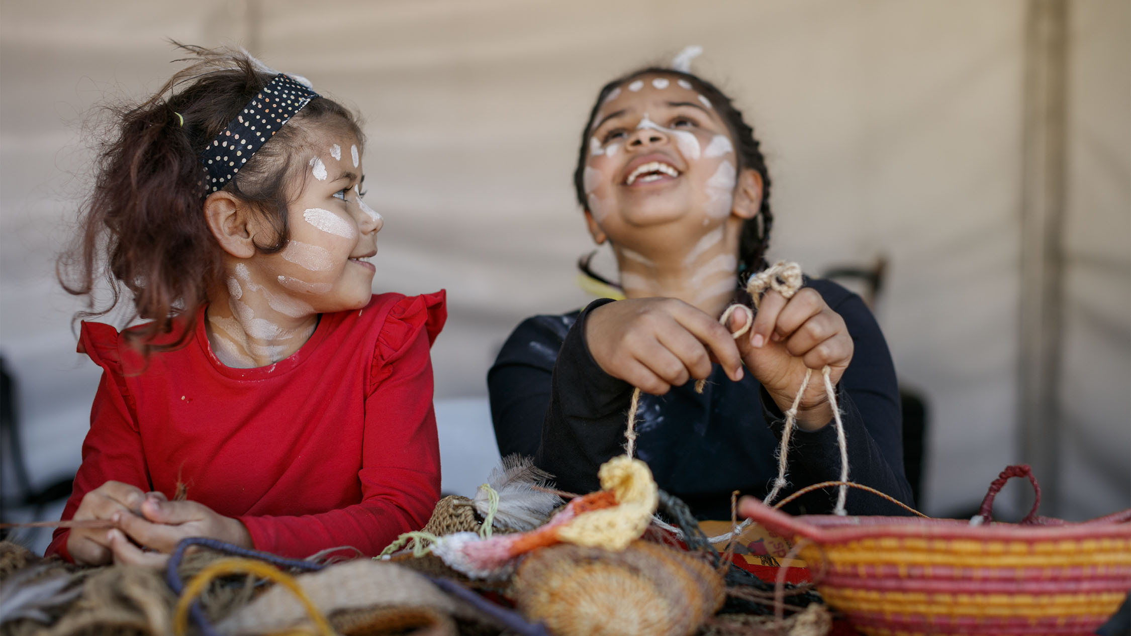 Two kids in Indigenous face paint doing craft.