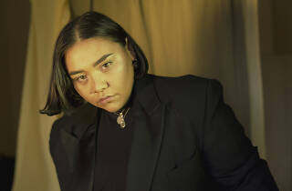 Artist Kira Puru wearing black in front of a yellow curtain.