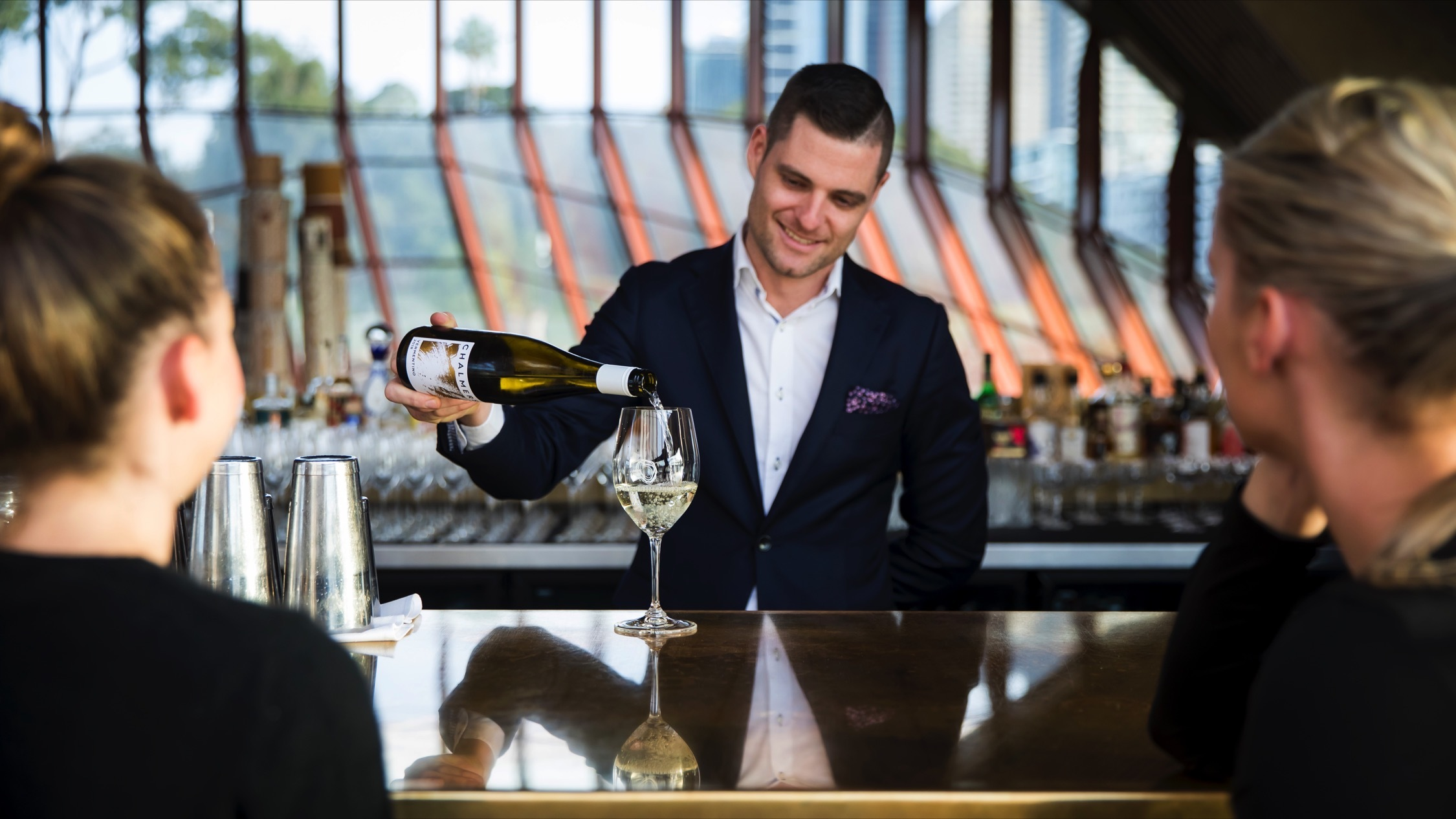 Person pouring glass of wine at Bennelong