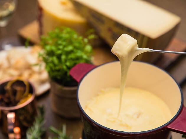 A pot of cheese fondue being eaten