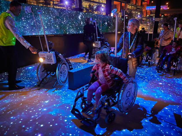 Kids using wheelchairs at a Vivid Light installation.
