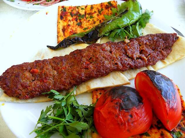 Meat on a white bread wrap with lettuce and tomato, Adana kebab