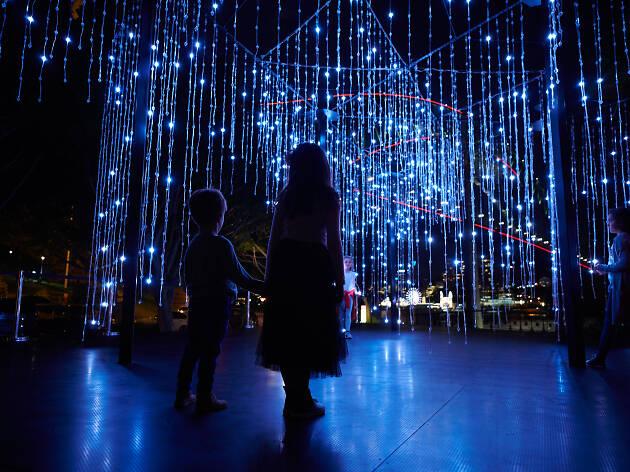 Kids standing under a Vivid Light installation.