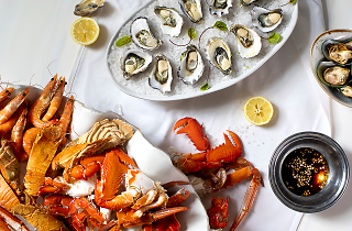 A birdseye view of a table with white table cloth and plates with lobsters, crabs, balmain bugs, oysters on ice, mussels and lemon halves, with dipping sauce