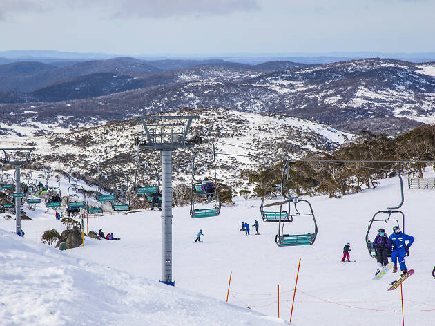 People enjoying a day of skiing and snowboarding at Blue Cow ski resort in Perisher.