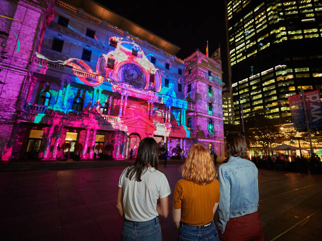 People looking at the light display on the facade of Customs House during Vivid Sydney.